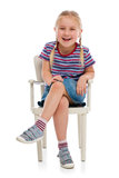 Smiling girl sitting on a chair Royalty Free Stock Photos