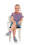 Smiling girl sitting on a chair Royalty Free Stock Photo