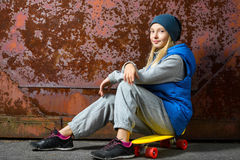 Smiling girl sitting on color plastic penny board Stock Photography