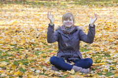 Smiling girl sitting on fallen leaves Stock Photos