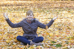 Smiling girl sitting on fallen leaves Royalty Free Stock Images