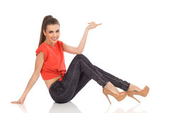 Smiling girl sitting on the floor and pointing Royalty Free Stock Photography