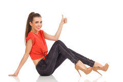 Smiling girl sitting on the floor and showing thumb up. Smiling girl in red top, black jeans and high heels sitting on the floor and showing thumb up. Full Stock Photography
