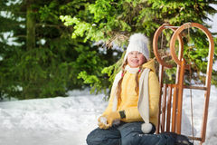 Smiling girl sitting in forest after sledging Stock Photos