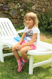 Smiling girl sitting on garden lounger Royalty Free Stock Photography