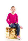Smiling girl is sitting on a gold pouffe. Royalty Free Stock Photography