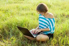 Smiling girl sitting on the grass in bright summer day and working on the computer. Using laptop outdoors, chatting with friends. Stock Photos