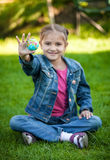 Smiling girl sitting on grass and holding Earth ball at hand Stock Photography