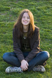 Smiling girl sitting on the grass Stock Photo