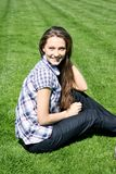 Smiling girl sitting on the green grass Royalty Free Stock Images
