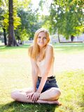 Smiling girl sitting on green grass outdoors. Looking at camera. Outdoor in nature royalty free stock photography