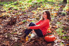 Smiling girl sitting on the ground covered with dry autumnal fol. Cute girl sitting on the ground covered with dry autumnal foliage with pumpkin and corn in Royalty Free Stock Images