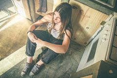 Smiling girl sitting on the kitchen floor. Funny picture of a girl in the kitchen. Social network style photo royalty free stock photography