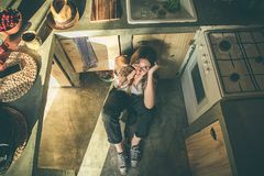 Smiling girl sitting on the kitchen floor. Funny picture of a girl in the kitchen. Social network style photo royalty free stock photo