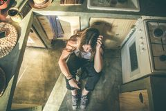 Smiling girl sitting on the kitchen floor. Funny picture of a girl in the kitchen. Social network style photo stock images