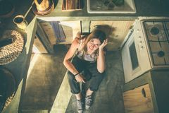 Smiling girl sitting on the kitchen floor. Funny picture of a girl in the kitchen. Social network style photo stock photos