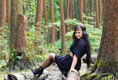 Smiling girl sitting on a log in the green forest Stock Images