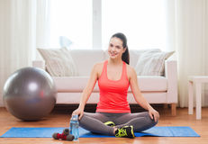 Smiling girl sitting on mat with sports equipment. Fitness, home and diet concept - smiling teenage girl sitting on mat with sports equipment at home Royalty Free Stock Images