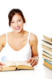 Smiling girl sitting near the pile of books. Stock Photo