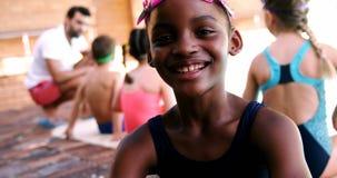 Smiling girl sitting near poolside stock video