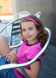 Smiling girl sitting in outdoor aluminium chair Royalty Free Stock Photography