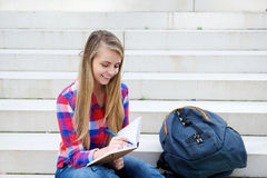 Smiling girl sitting outside writing in book Royalty Free Stock Photo