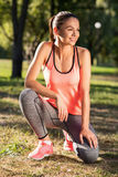 Smiling girl sitting in the park after morning exercises Royalty Free Stock Photography