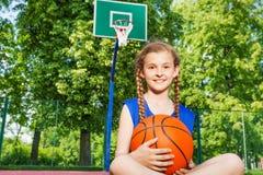 Smiling girl sitting on playground holding ball Stock Photos