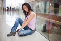 Smiling girl is sitting in the shopping mall. Portrait of a smiling girl girl that is sitting on the floor in the shopping mall Royalty Free Stock Images