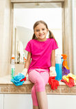 Smiling girl sitting on sink at bathroom while doing cleaning Stock Photos