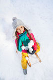 Smiling girl sitting on sledge with snowballs Stock Image