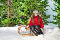 Smiling girl sitting on sledge in winter forest Royalty Free Stock Photos