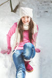 Smiling girl sitting on snow winter background Stock Photography