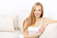Smiling girl sitting on sofa Stock Photo