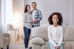 Smiling girl sitting on the sofa. In high spirits. Pretty delighted curly-haired girl smiling and sitting on the couch and her parents standing in the background Stock Photography
