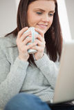 Smiling girl sitting on a sofa holding a cup of coffee and looking at laptop Stock Photo