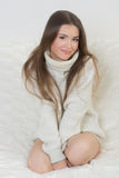 Smiling girl sitting on sofa Stock Images