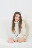 Smiling girl sitting on sofa Royalty Free Stock Photography