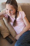 Smiling girl sitting on sofa in the living room Royalty Free Stock Image