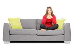 Smiling girl sitting on a sofa and looking at camera Stock Photography