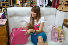 A smiling girl sitting on a sofa next to her shopping bags on a shop background. A girl looking at her purchases. Stock Image