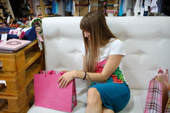 A smiling girl sitting on a sofa next to her shopping bags on a shop background. A girl looking at her purchases. Stock Photos