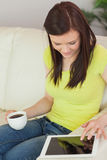Smiling girl sitting on a sofa using a tablet pc and holding a c Stock Image