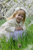 Smiling girl sitting among spring blossom garden Royalty Free Stock Photos