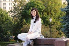 Smiling girl sitting on stone bench. Smiling brunette girl sitting on stone bench outdoor photo Royalty Free Stock Photography