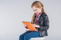 Smiling girl sitting on stool and using digital tablet Stock Image