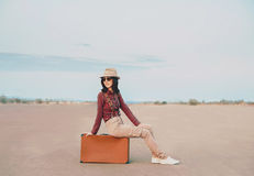 Smiling girl sitting on suitcase on road Stock Images