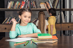 Smiling girl sitting at table with classmates looking for books behind Stock Photography