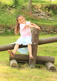 Smiling girl sitting on timber Royalty Free Stock Photography