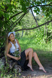 Smiling girl sitting on the wood and holding bunch of flowers Royalty Free Stock Images